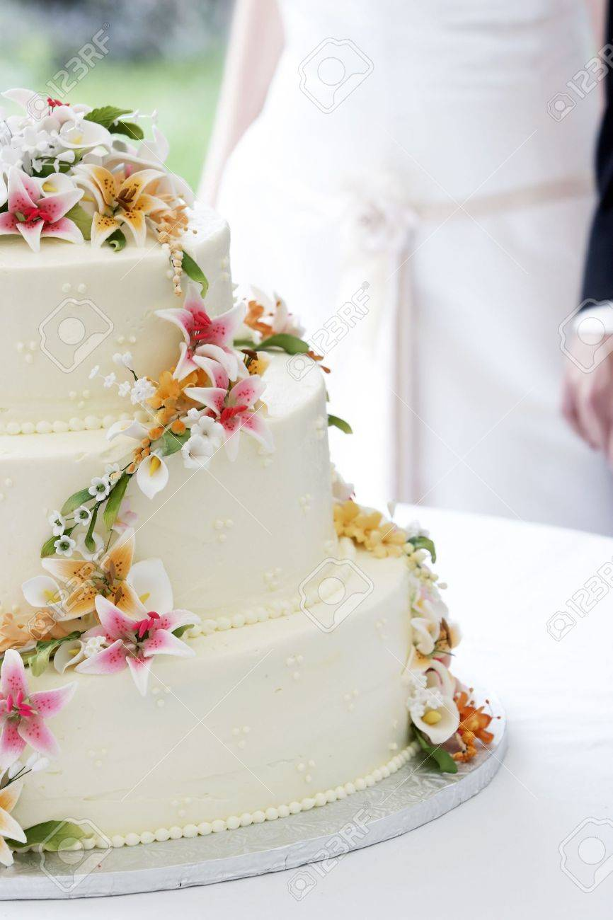 A Wonderful Wedding Cake With The Bride And Groom In The Background ...