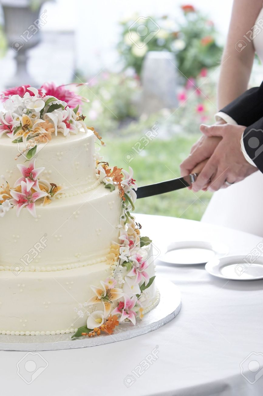A Wonderful Wedding Cake With The Bride And Groom Cutting The ...