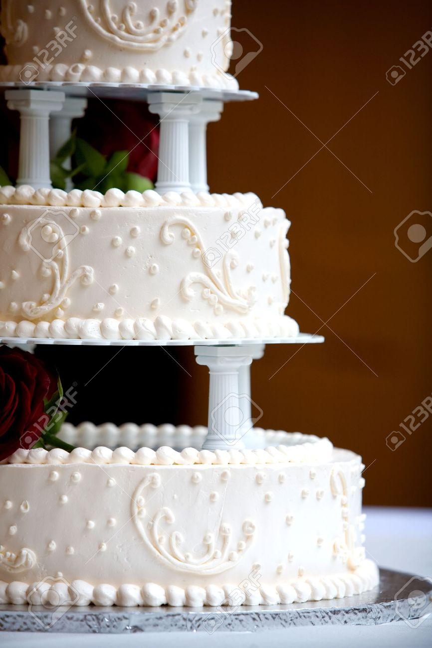 A White Wedding Cake With Three Levels And Red Roses Stock Photo ...