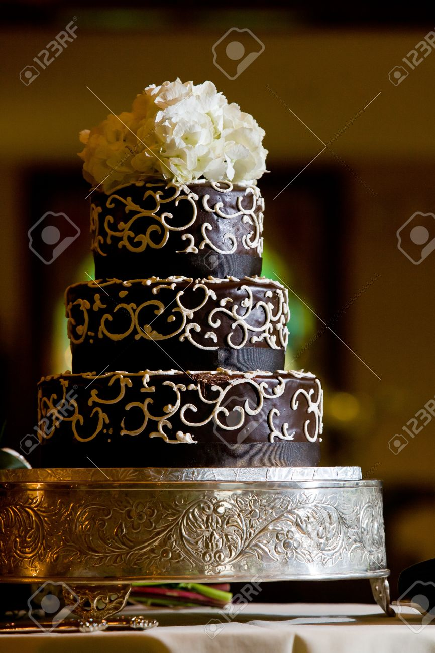 A Chocolate Wedding Cake With White Frosting Details And Flowers