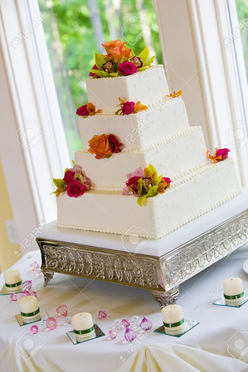 A White Wedding Cake With Multiple Layers And Flowers On A Silver ...