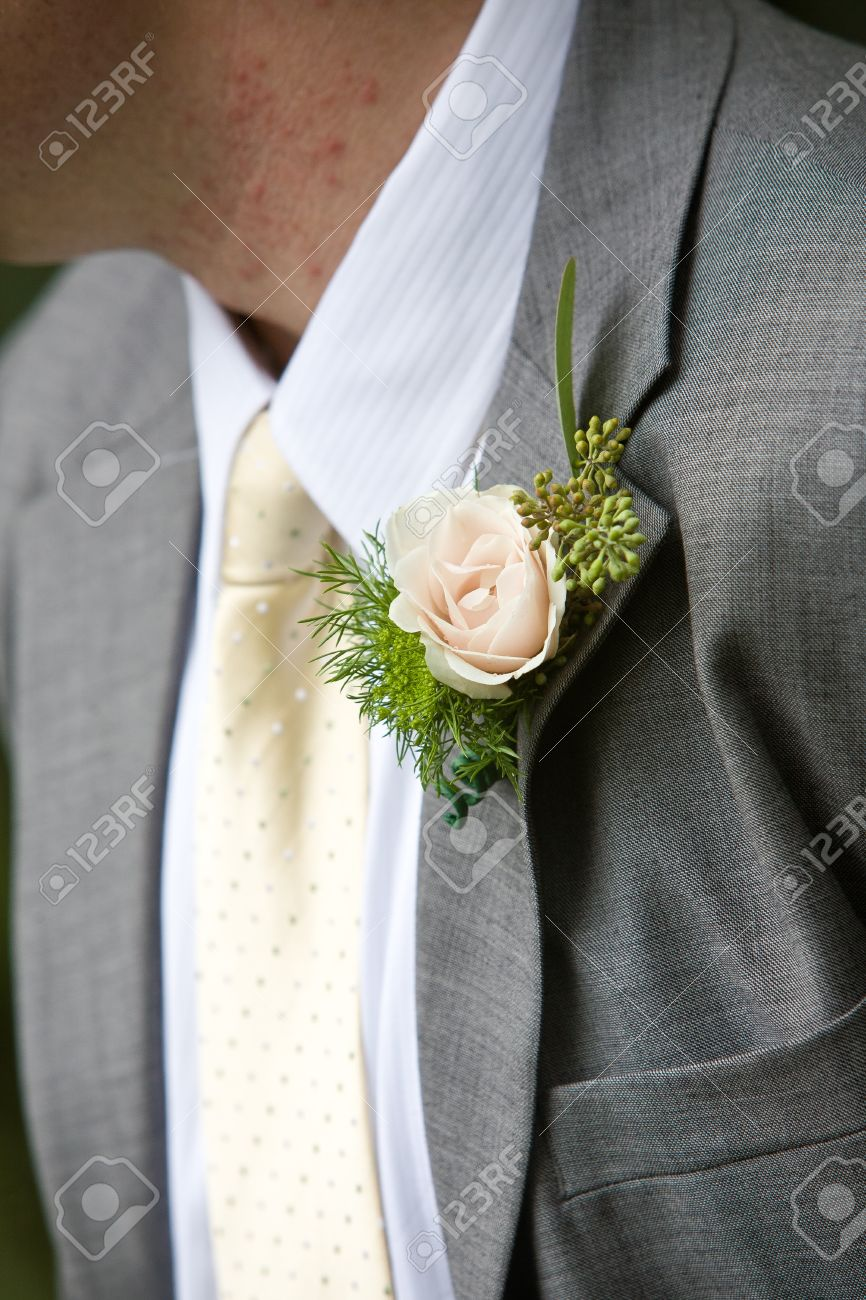 a grooms wedding boutonniere in pink and green lapel flower