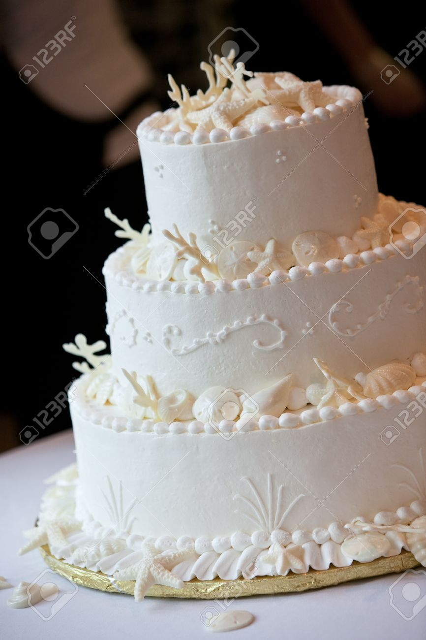 a white ocean themed wedding cake with miniature seashell design and details - 12958899