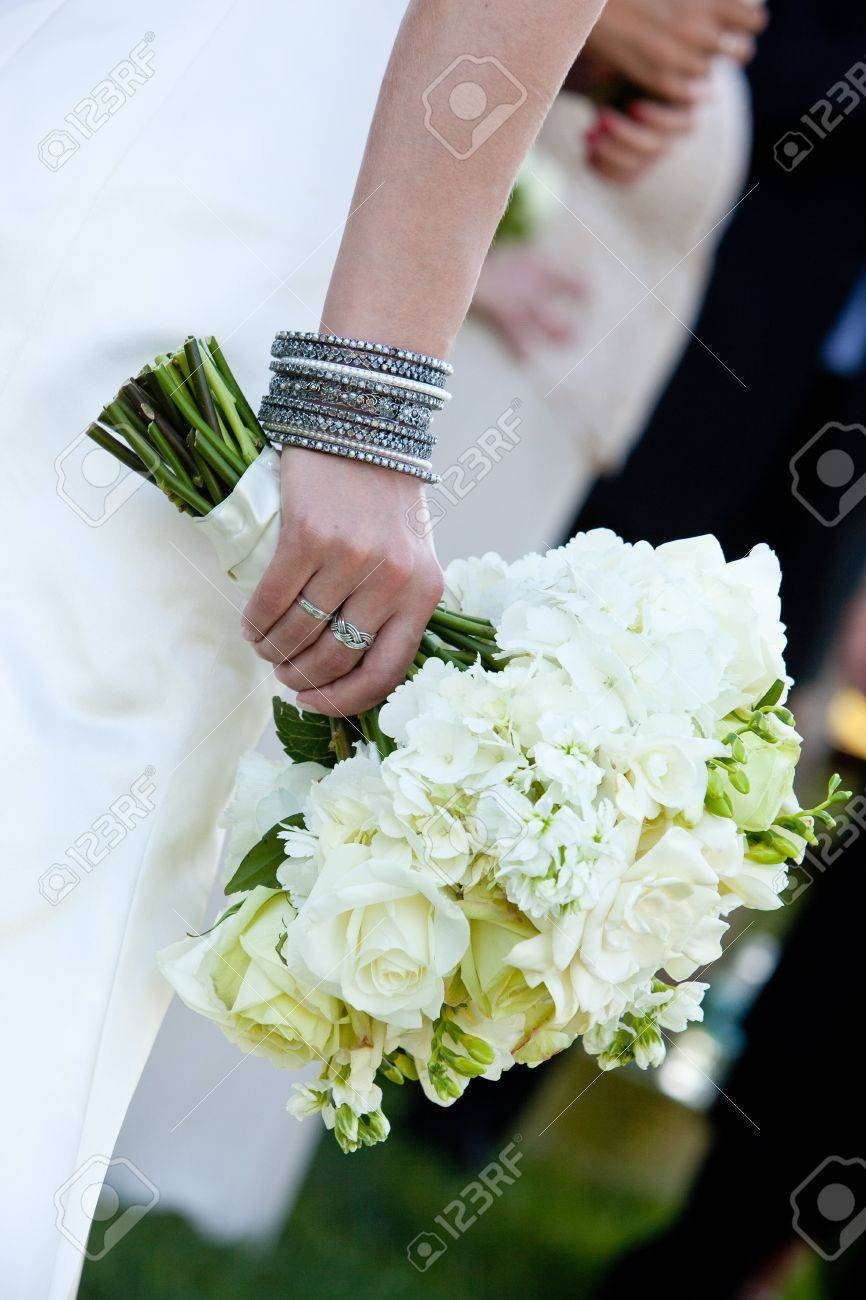 A Bride Holding A Green And White Wedding Bouquet Of Flowers Stock