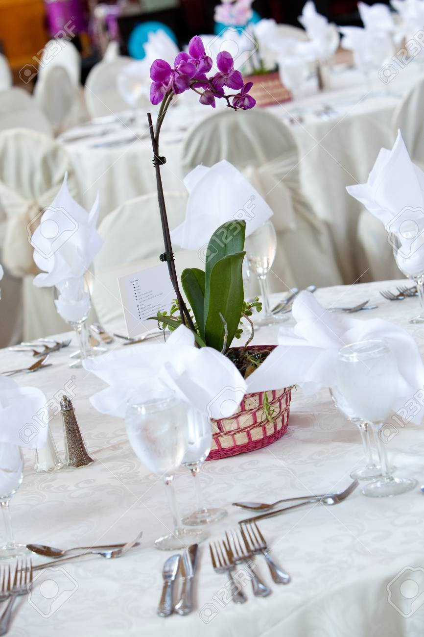 A Purple Orchid Flower Centerpiece On A White Wedding Table Stock ...