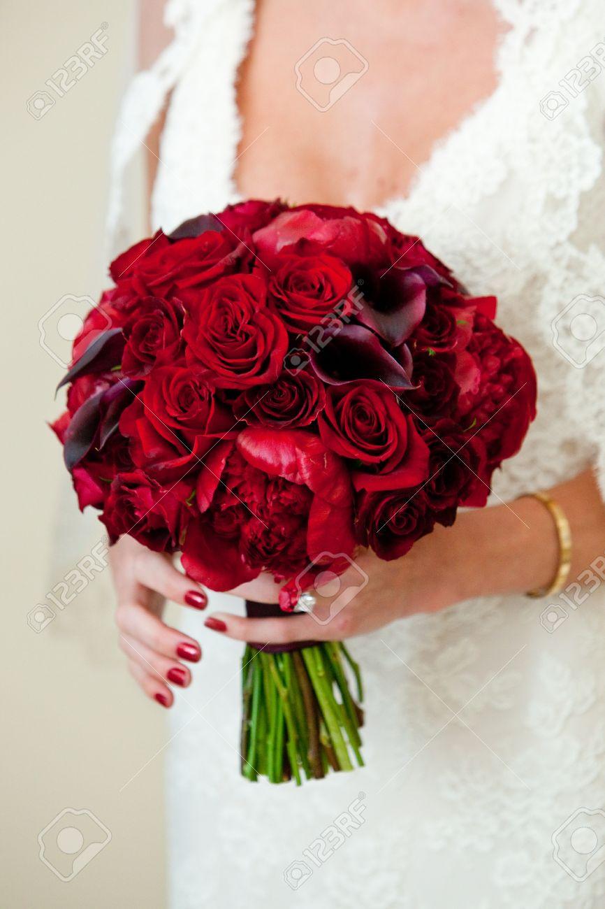 Foto de archivo , una novia la celebración de su hermosa flor de color rojo y un ramo de rosas