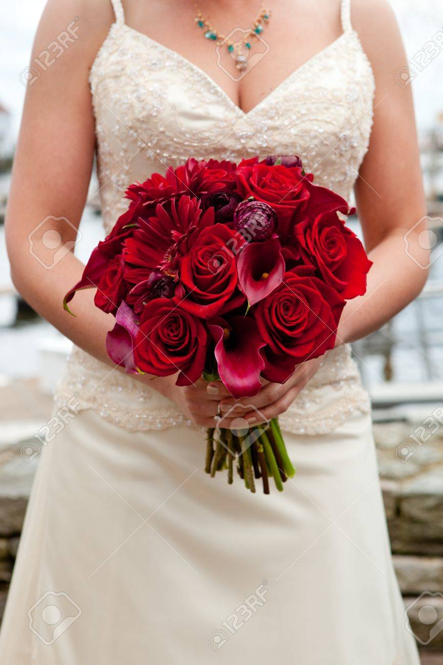 A Bride Holding Her Red Wedding Bouquet Of Flowers Stock Photo ...