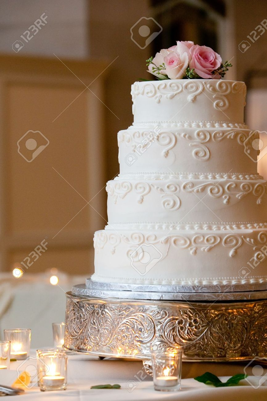 A Multi Level White Wedding Cake On A Silver Base And Pink Flowers ...