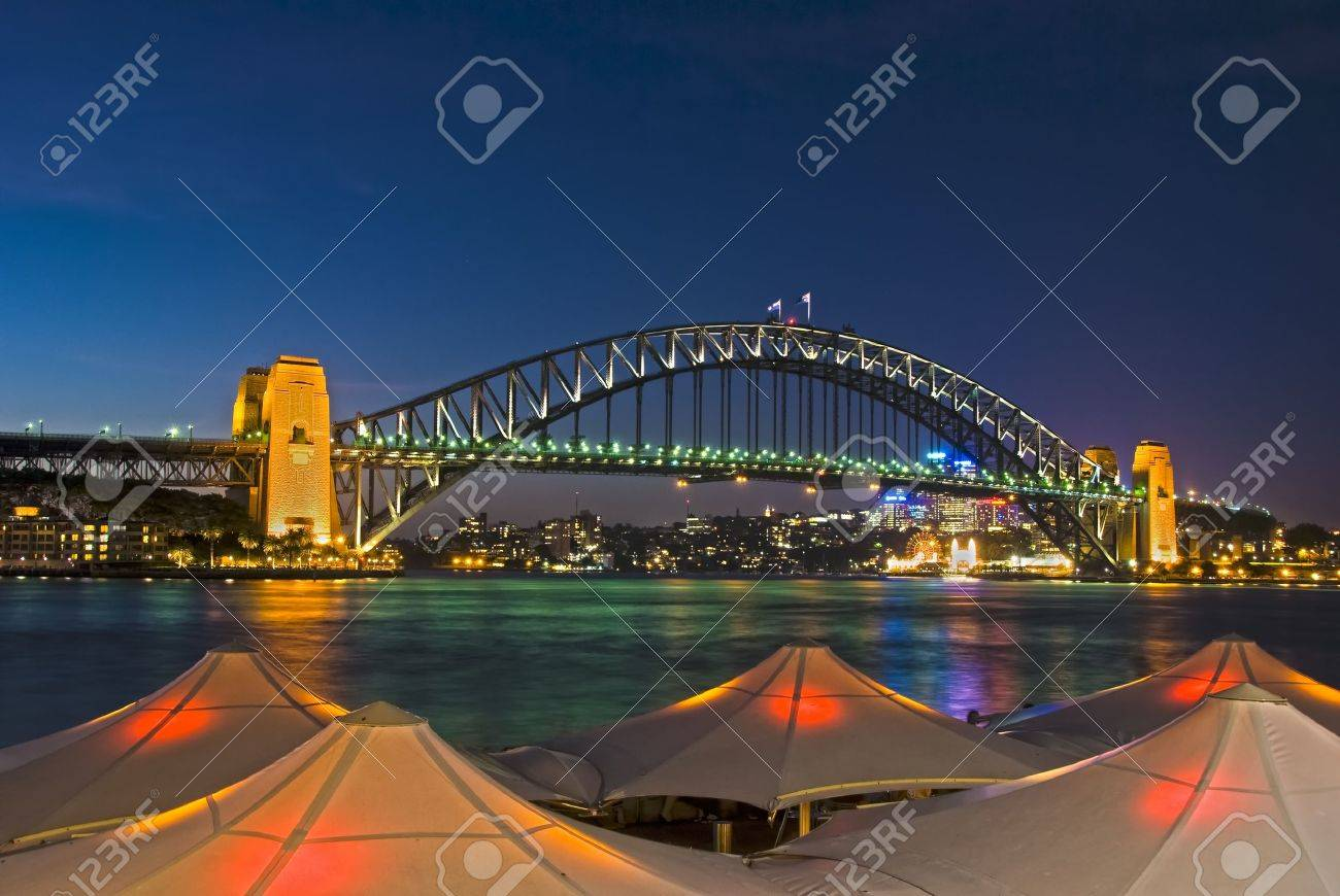 Sydney Harbour Bridge viewed from Circular Quay from behind lighted umbrellas Stock Photo - 9912907
