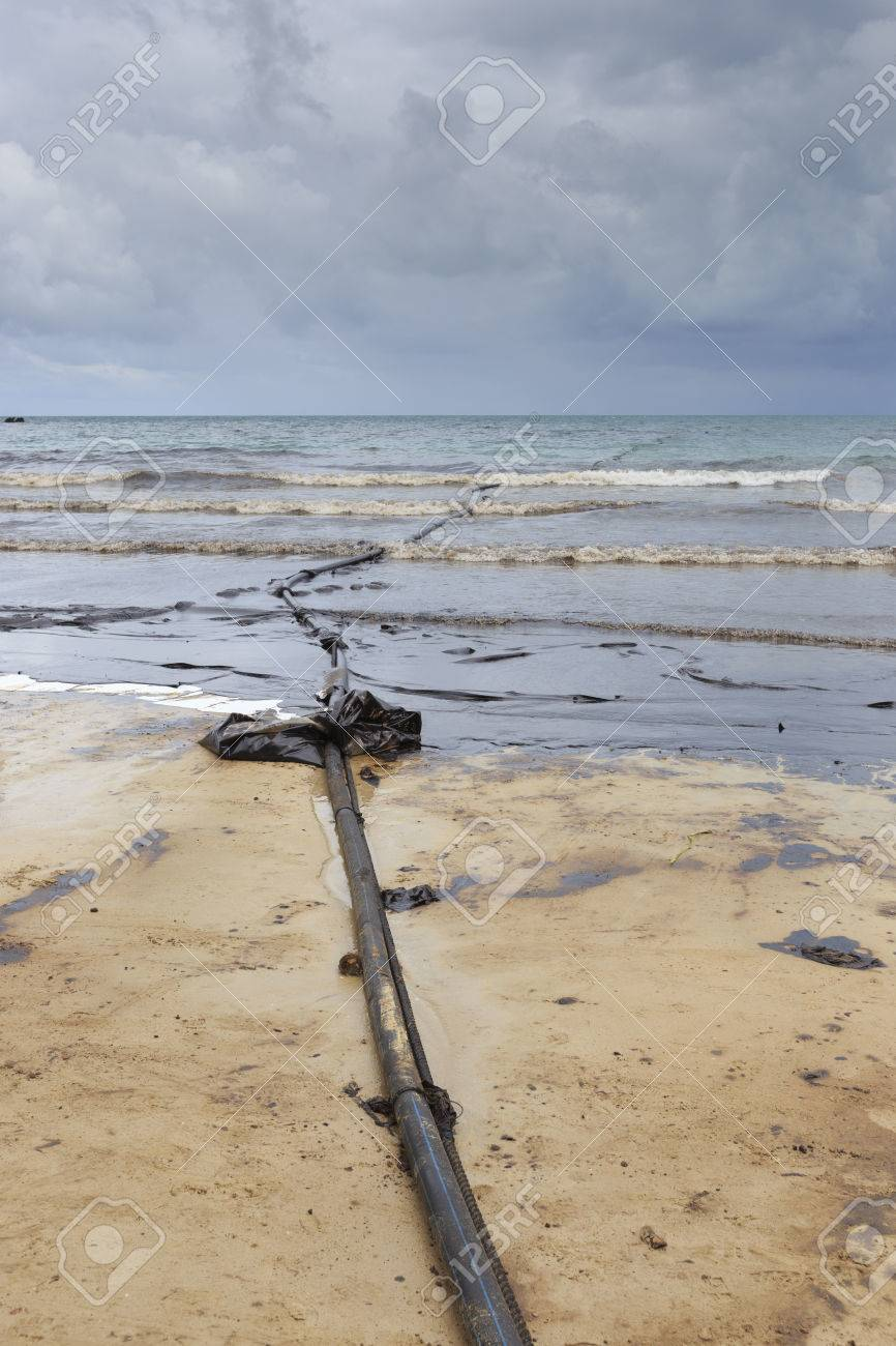 pipeline on dirty beach as tool to suck crude oil on clean-up
