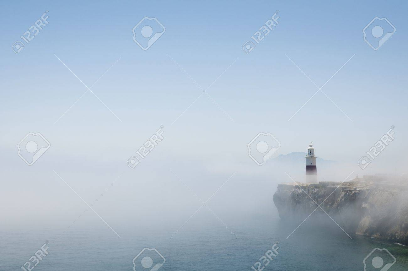Gibraltars lighthouse at Europa Point standing in the mist with Africa in the distance. Stock Photo - 13978058