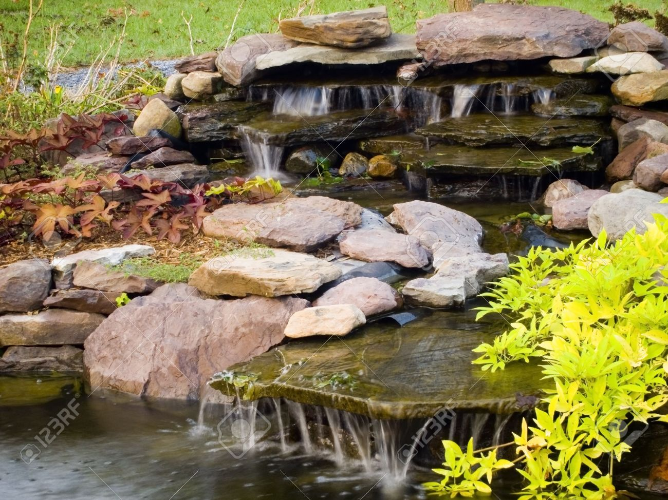 Outdoor ornamental plants - Water Feature With Rocks Ornamental Plants And Flowing Waterfalls Stock Photo 548982