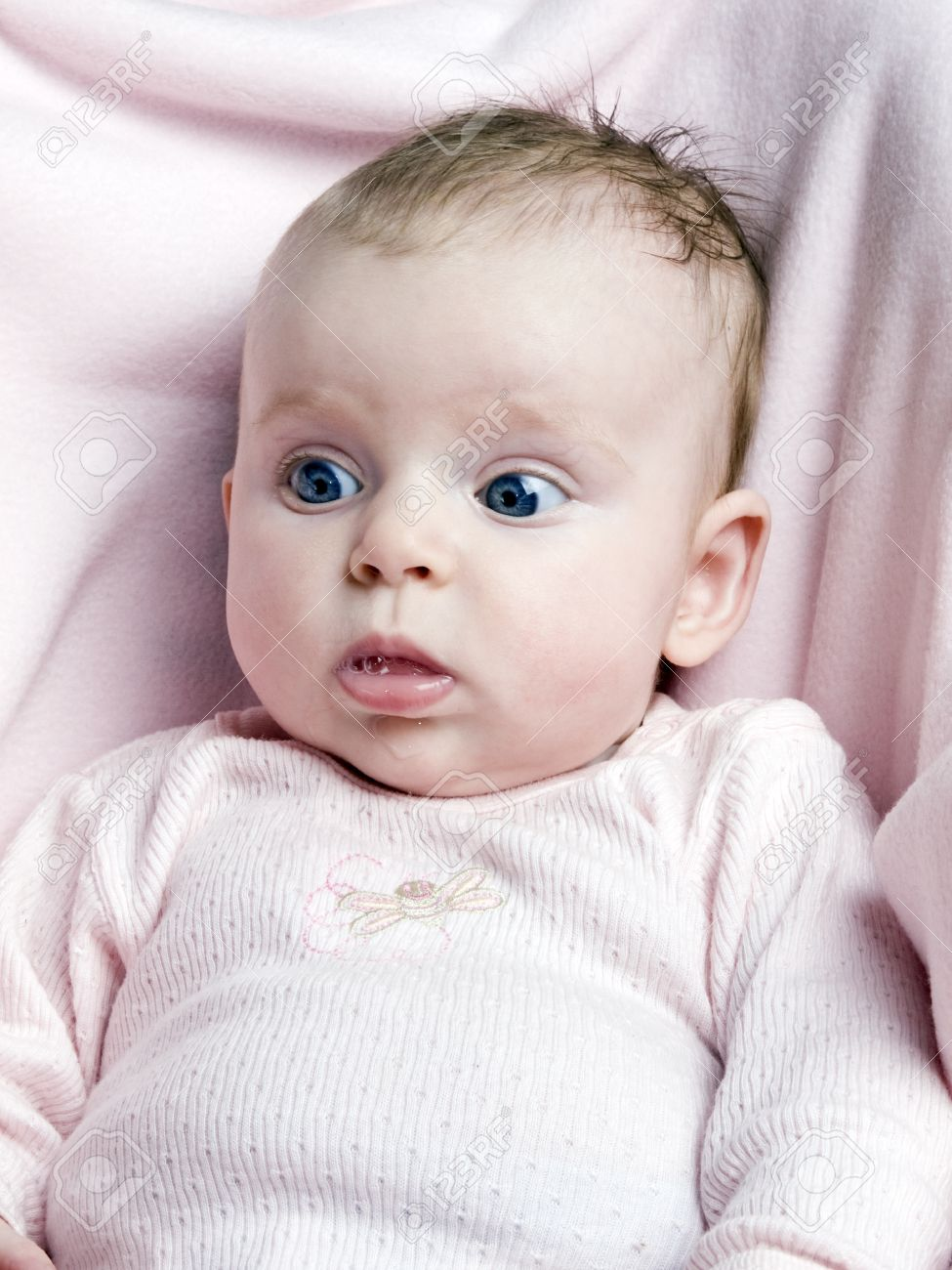 Cute newborn baby girl with big blue eyes on pink background stock photo 9748869
