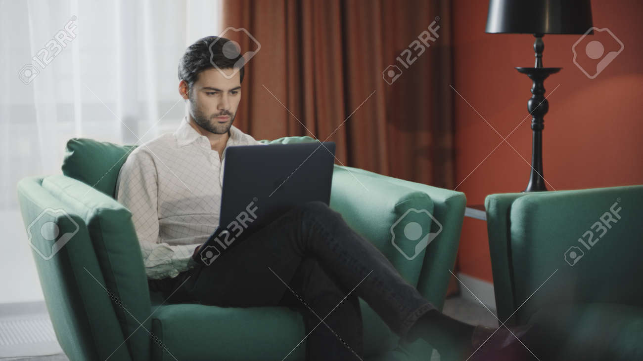 Handsome businessman working laptop computer in luxury hotel. Business man working computer at remote workplace. Remote worker typing notebook at modern apartment. - 154570870