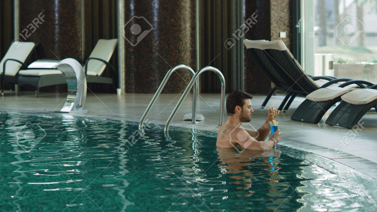 Attractive man drinking cocktail at luxury pool indoor. Sexy guy relaxing with alcohol cocktail at pool. Handsome man resting at luxury spa with alcohol. - 160842250