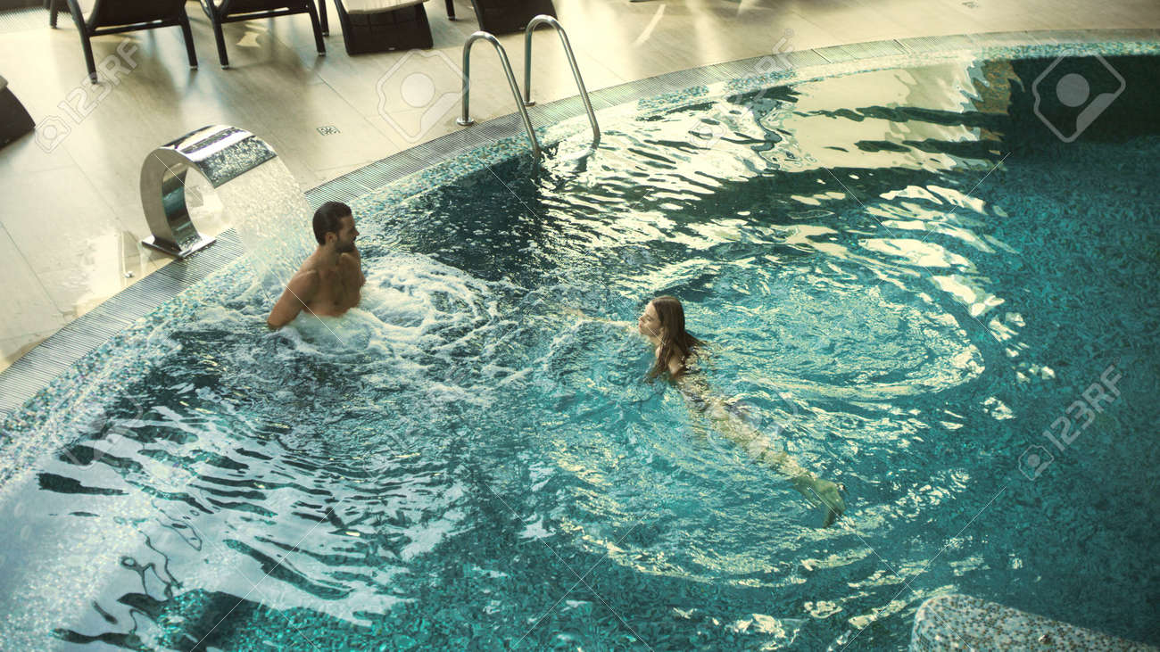 Top view of cheerful couple enjoying swimming at wellness resort. Happy couple bathing at luxury spa together in slow motion. Relaxed man and woman resting in whirlpool bath indoor. - 160490215