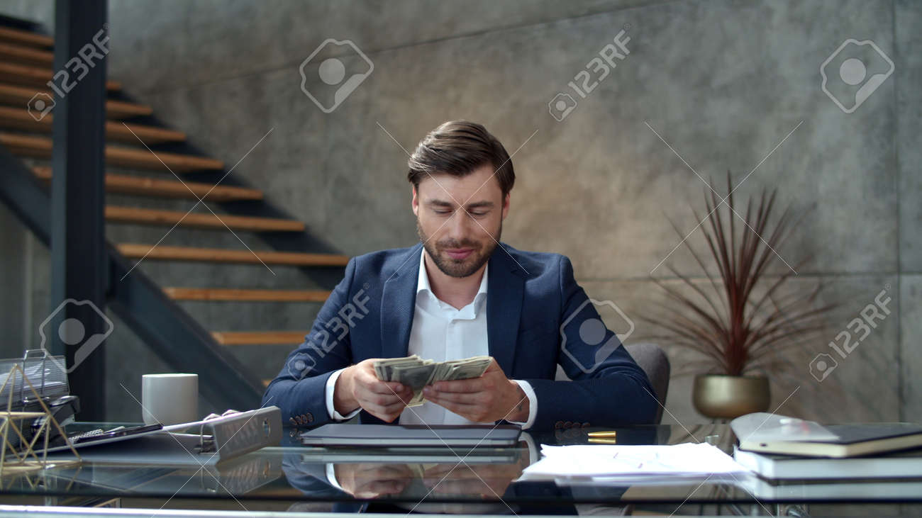 Happy businessman throwing money away in modern office. Portrait of successful business man counting money at workplace. Joyful man rejoicing good deal in office in slow motion - 162267989