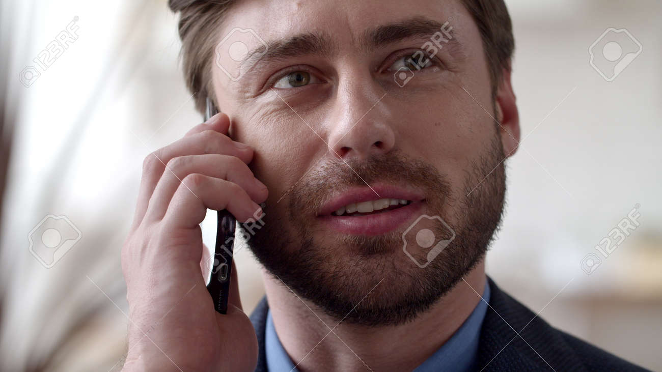 Closeup smiling business man speaking phone emotionally at home. Attractive man talking mobile phone in slow motion. Portrait of joyful guy calling cellphone at remote office. - 162271007