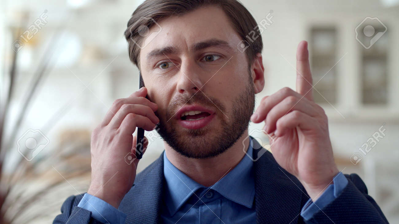 Closeup focused business man getting new idea at remote office. Young guy talking on cell phone at home in slow motion. Serious man having successful phone conversation at remote workplace. - 162271086