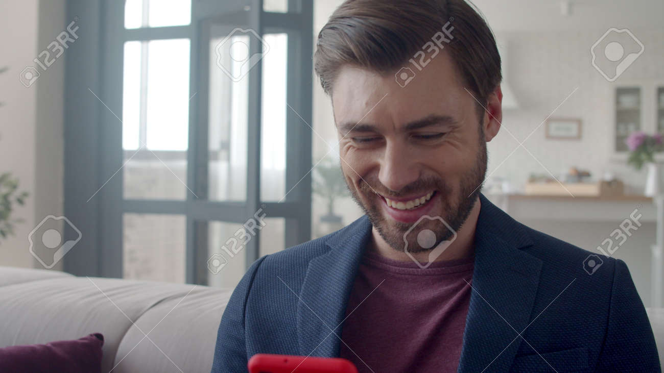 Closeup handsome business man laughing with phone at home. Portrait of smiling guy reading funny text on phone in flat. Joyful man surfing internet on smartphone on sofa. Guy reading funny email . - 162271088