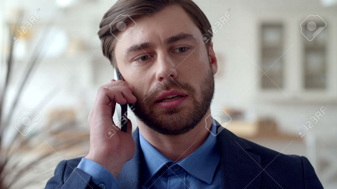 Closeup attractive business man making phone call at home. Portrait of focused guy talking on cellphone at remote office. Serious male freelancer speaking by phone at modern house. - 162271287