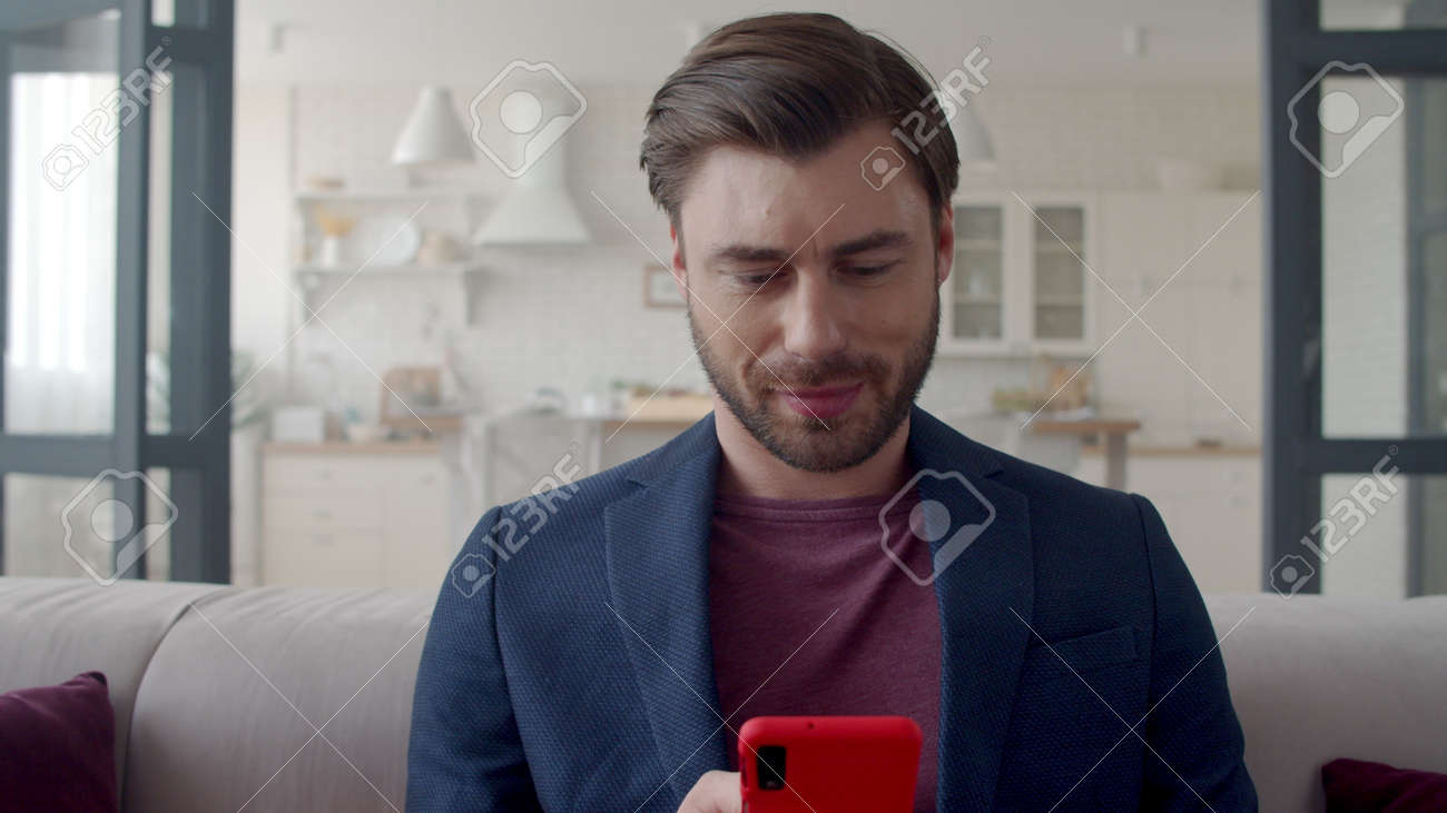 Closeup joyful business man surfing internet on cell phone at home office. Smiling man texting on smartphone in remote workplace. Portrait of freelancer guy reading email on phone in livingroom. - 162271330