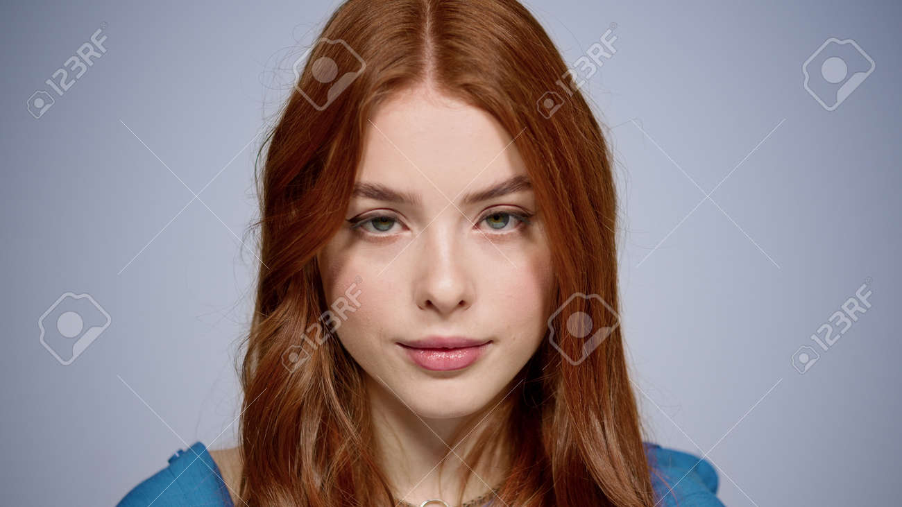 Charming girl raising head up in studio. Portrait of beautiful female person showing hush sign indoors. Closeup sensual ginger hair woman looking at camera on gray background. - 158355051