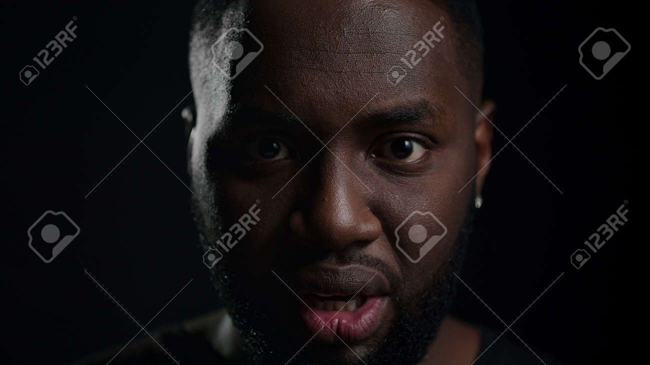 Closeup african american man crying on black background. Portrait of frustrated male person looking at camera in studio. Shocked afro guy yelling indoors. - 158355132