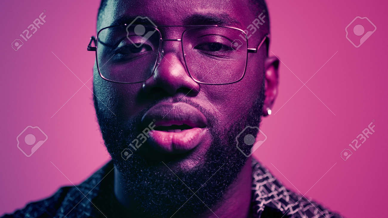 Closeup fancy afro guy staring at lenses indoors. Portrait of romantic male person flirting on pink background. African american guy sending kisses in studio. - 159609815