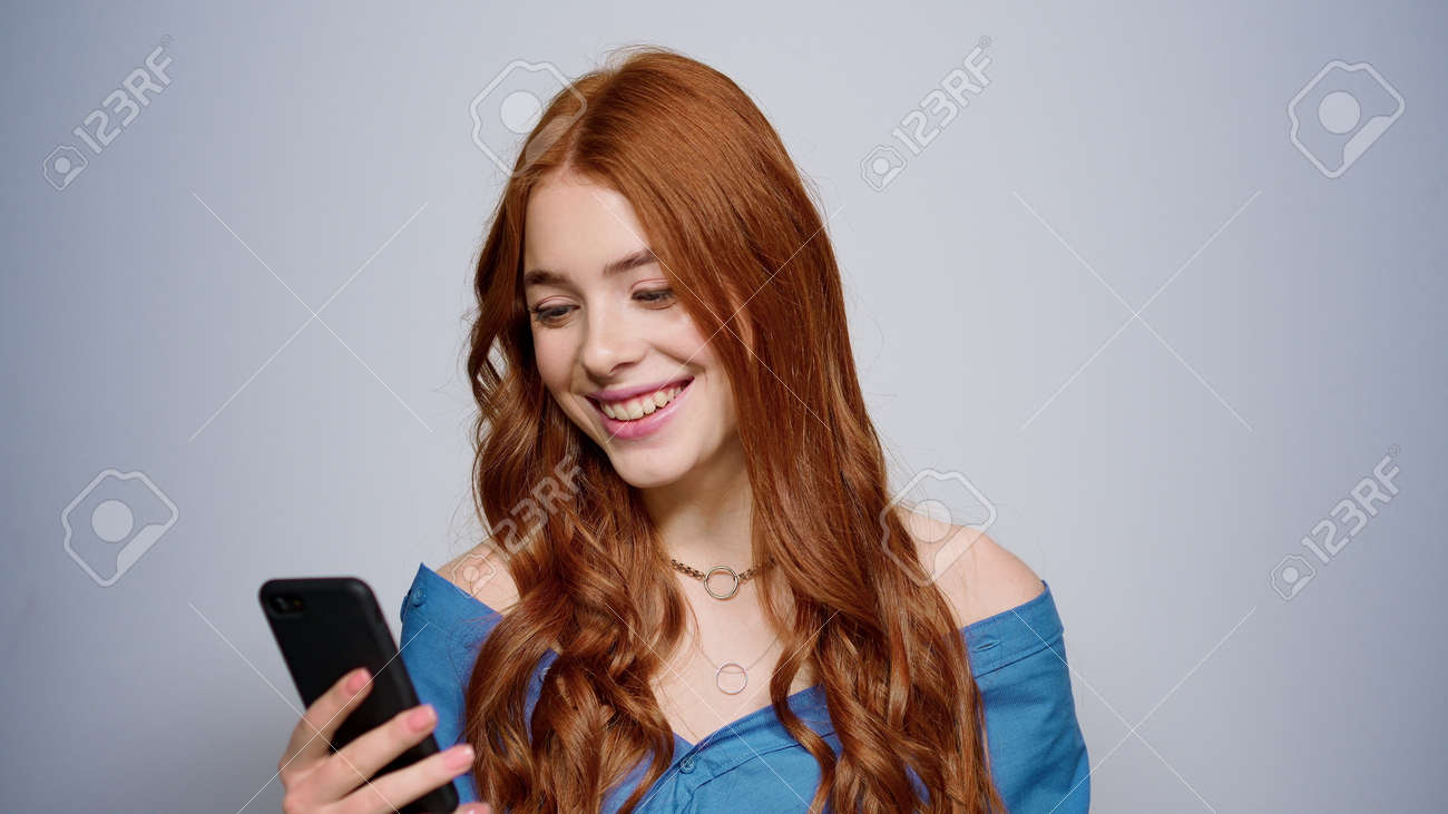 Red hair girl holding mobile phone in studio. Portrait of cheerful female person looking smartphone screen indoors. Closeup attractive woman getting good news on cellphone. - 159609837