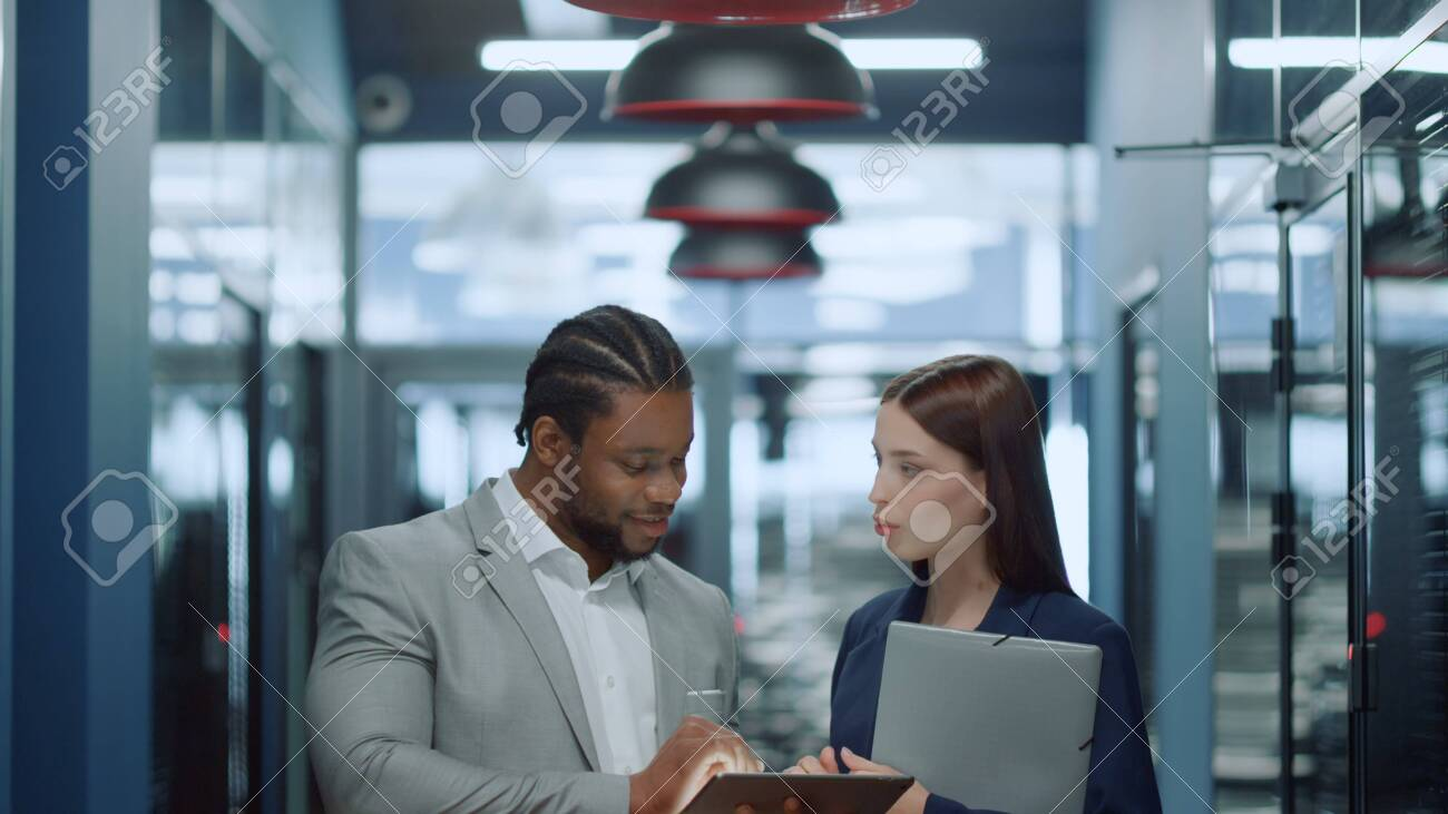Portrait of cheerful colleagues using tablet computer in corridor. Closeup happy man and woman talking in business center. Multi ethnic business people working with tablet in office corridor. - 158485727
