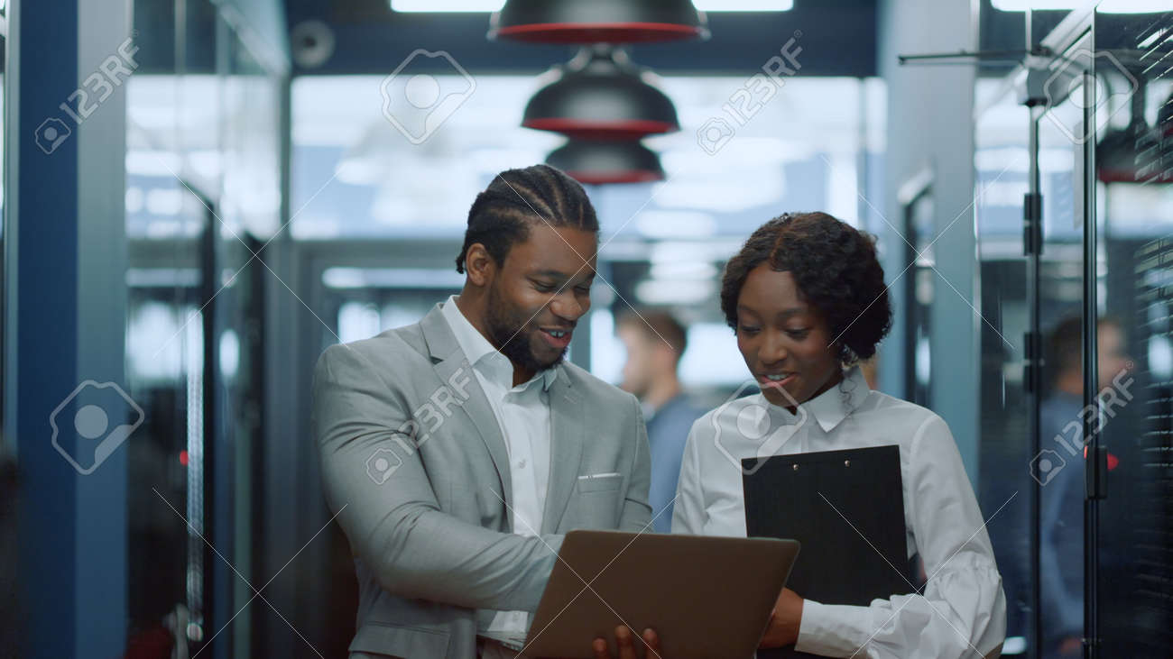 Portrait of smiling african business people using laptop in corridor. African american colleagues working in business center hallway. Cheerful afro couple discussing project in office interior - 158485720