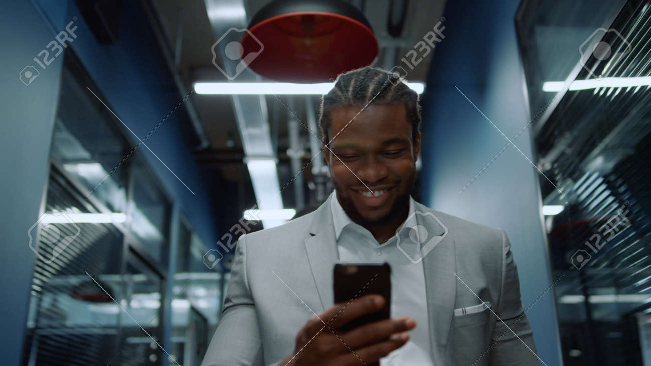 Portrait of smiling afro business man getting good news on mobile phone in office. Closeup happy african businessman reading message on smartphone in corridor. African american man laughing in hallway - 158485725
