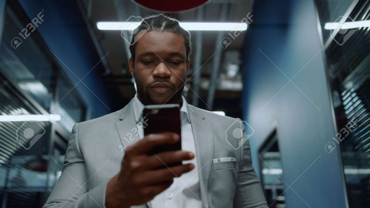 Portrait of serious afro business man texting message on mobile phone in business center. Focused businessman using smartphone in corridor. Closeup african american man walking in office hallway. - 158485757