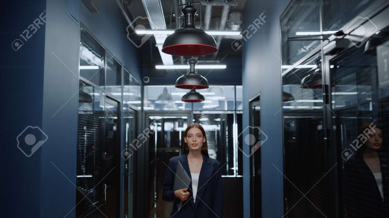Portrait of smiling businesswoman posing in office corridor. Closeup charming female manager looking at camera in office hallway. Positive business woman holding folder in business center interior. - 158542023