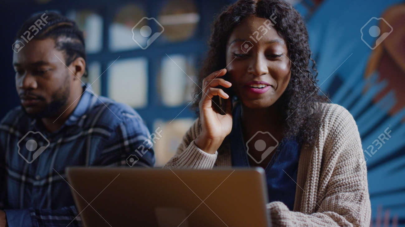 Closeup african american colleagues working at workplace in business center. Positive afro business woman talking phone in office. Portrait of smiling girl calling phone in creative coworking. - 158542089