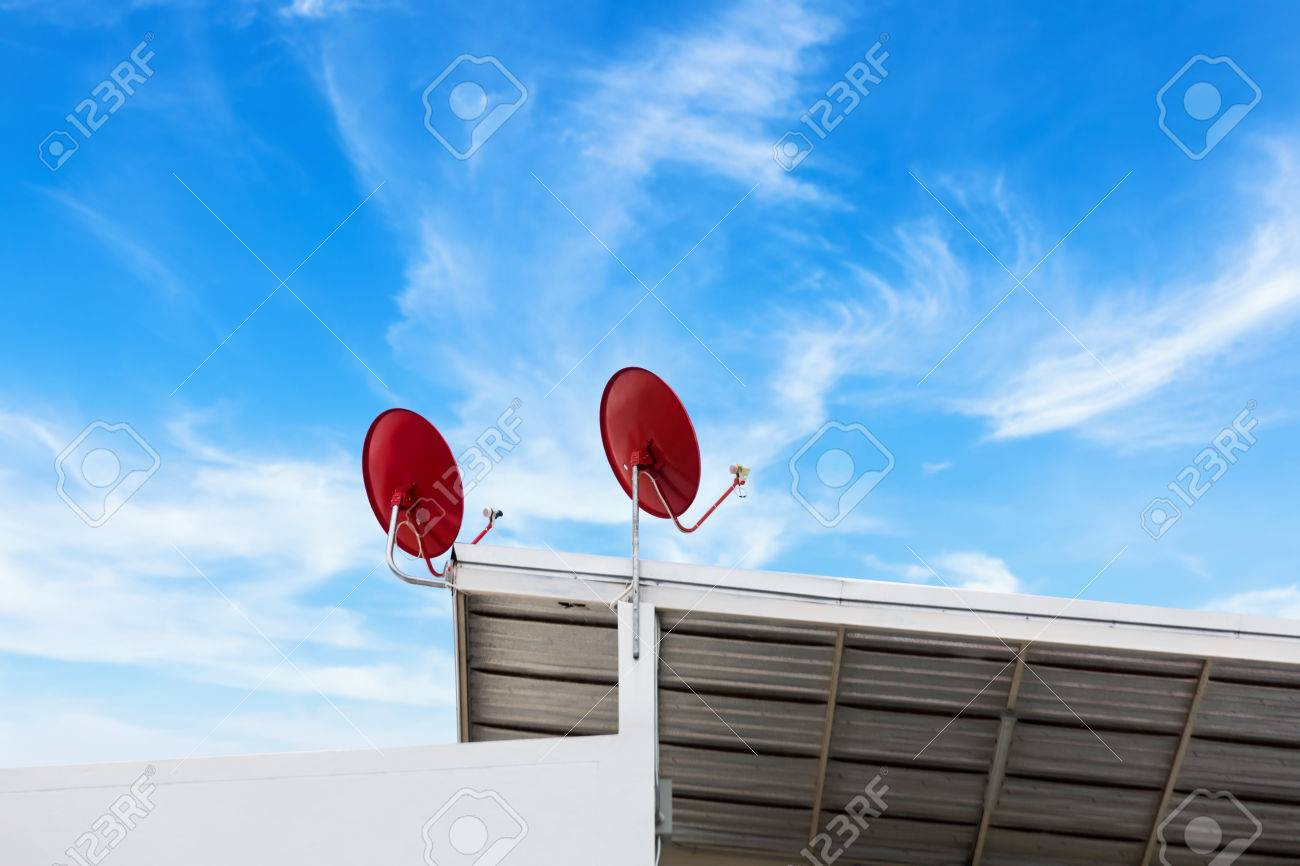 satellite dish and TV antennas on the house roof with blue sky