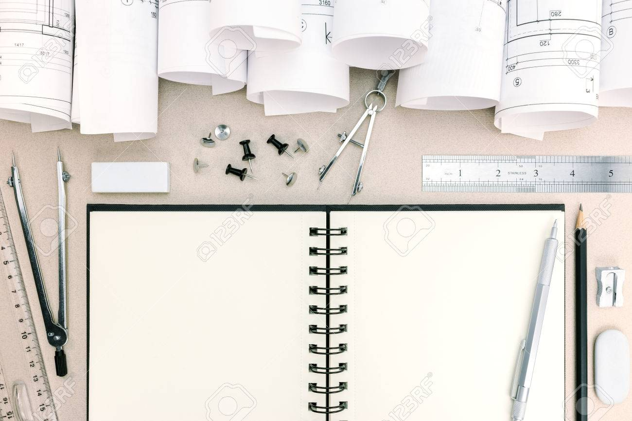 architect workspace with blueprints, notepad, drawing compass,