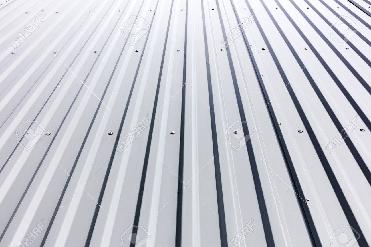 corrugated steel cladding with rivets on roof of industrial building