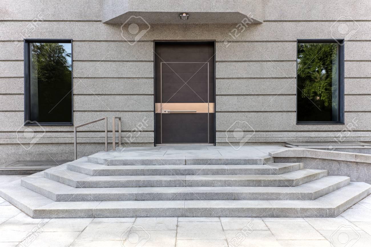 Closed Metal Front Door With Gray Stone Door Steps