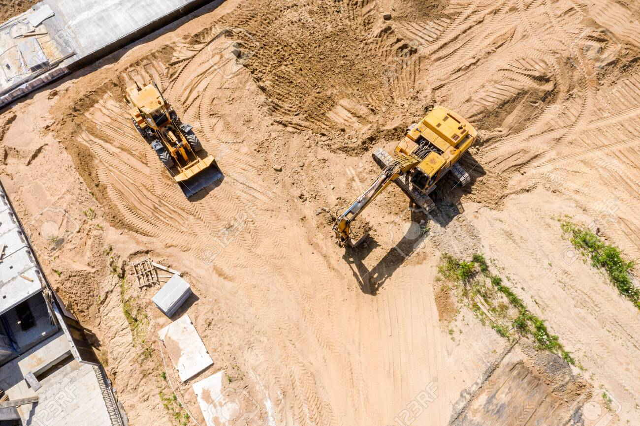 aerial top view of yellow industrial heavy machines moving ground at construction site - 128233960
