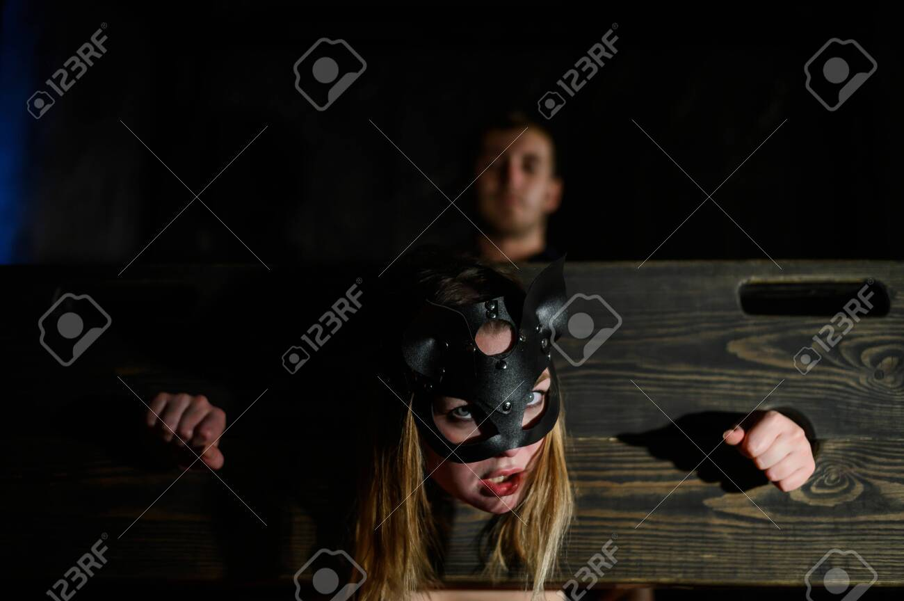tapes. A woman is imprisoned in a wooden pillory during games. BDSM Erotic fantasies. Subordination. Toys for adults. The mask of the cat. The man in the shirt dominates. - 132354795