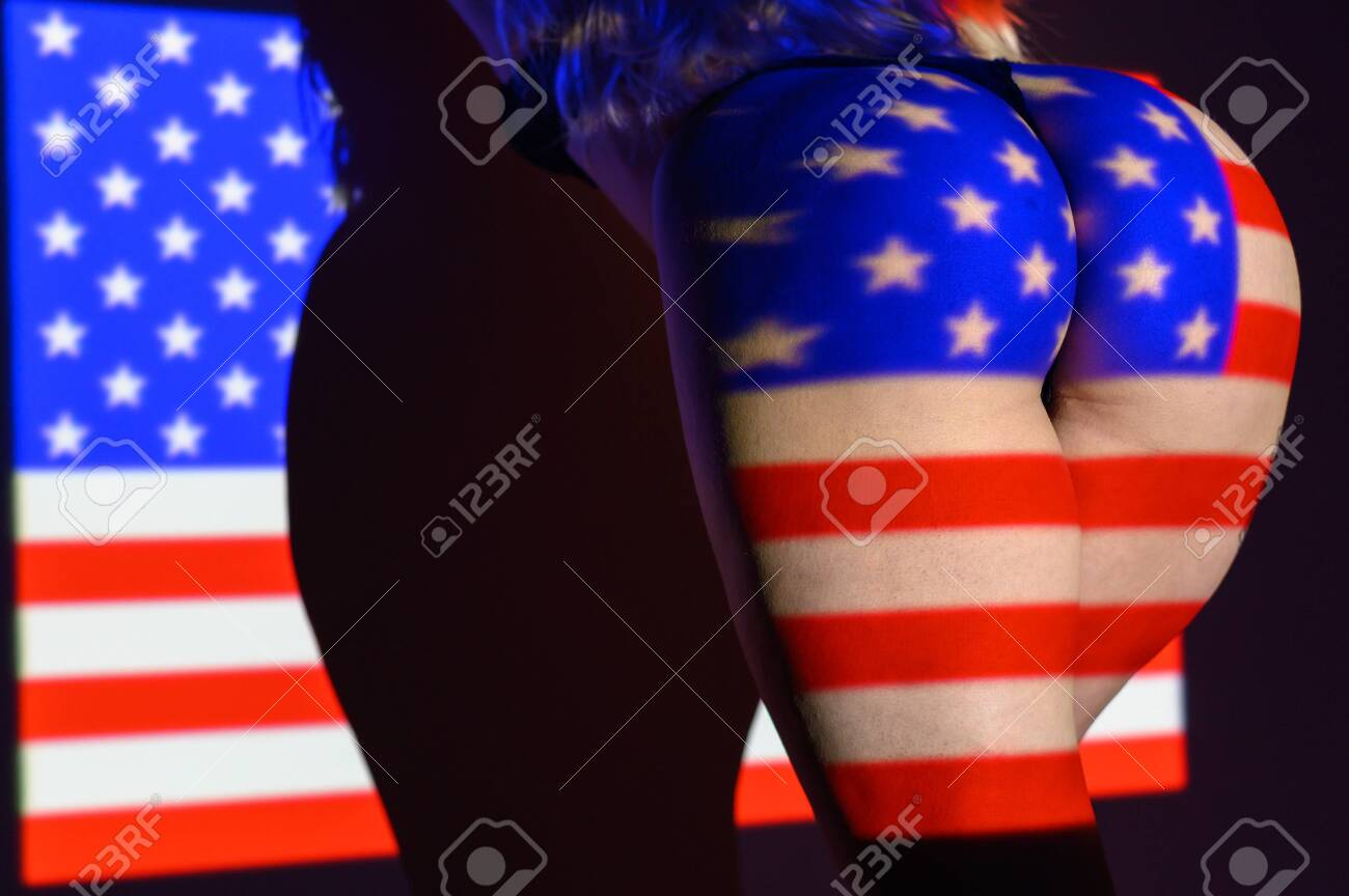 The projection of the flag of the United States of America on a beautiful large female ass. The projector shines with a flag on a female body. - 133947179