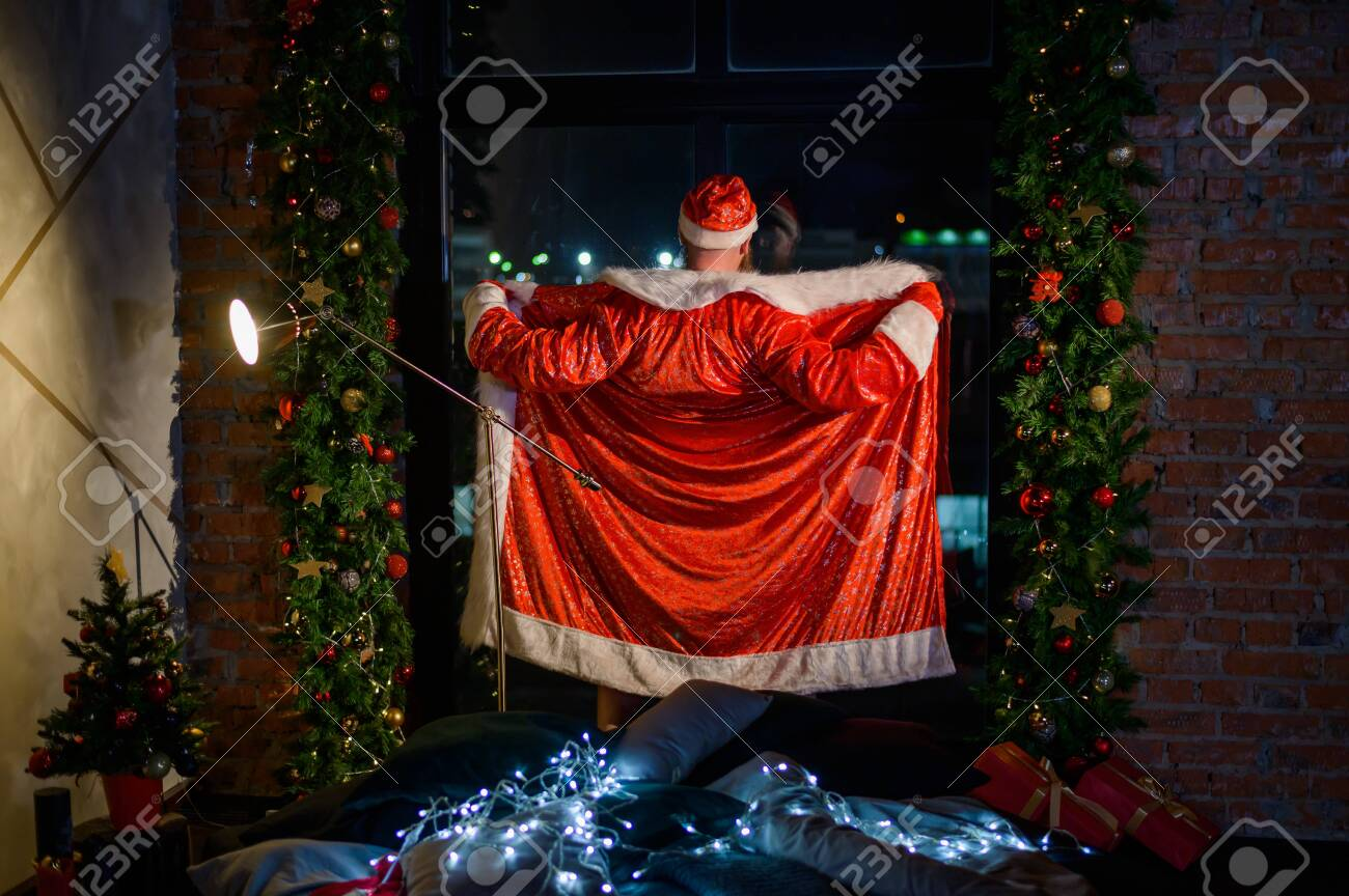 Humorous image of a man in a suit of Santa Claus showing striptease at the window. Bad Santa Claus opened his suit for a joke. Vulgar humor. - 133947443