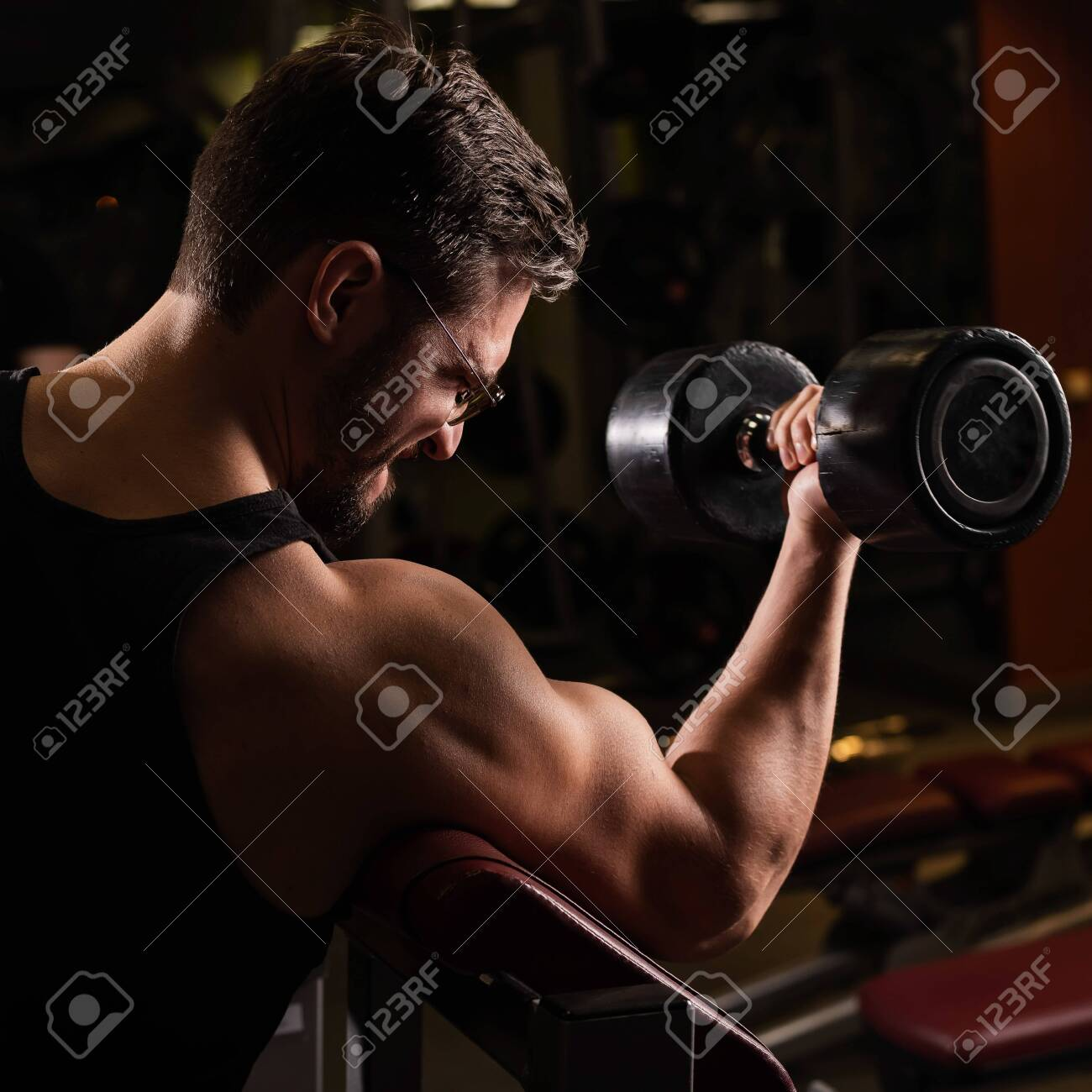 A handsome man with glasses doing an exercise for biceps with a barbell. The guy is engaged in bodybuilding. Trainer in the gym with muscular arms. - 142279774