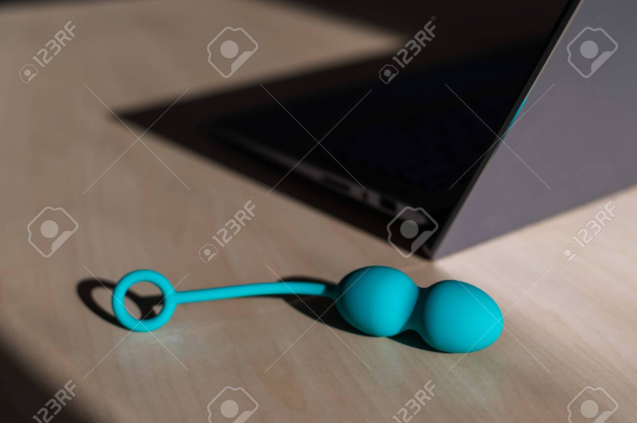 Blue silicone vaginal kegel balls on a table next to a laptop. Sex toy for building is synchronized with a computer. Intimate muscle trainer for women health. - 146952953