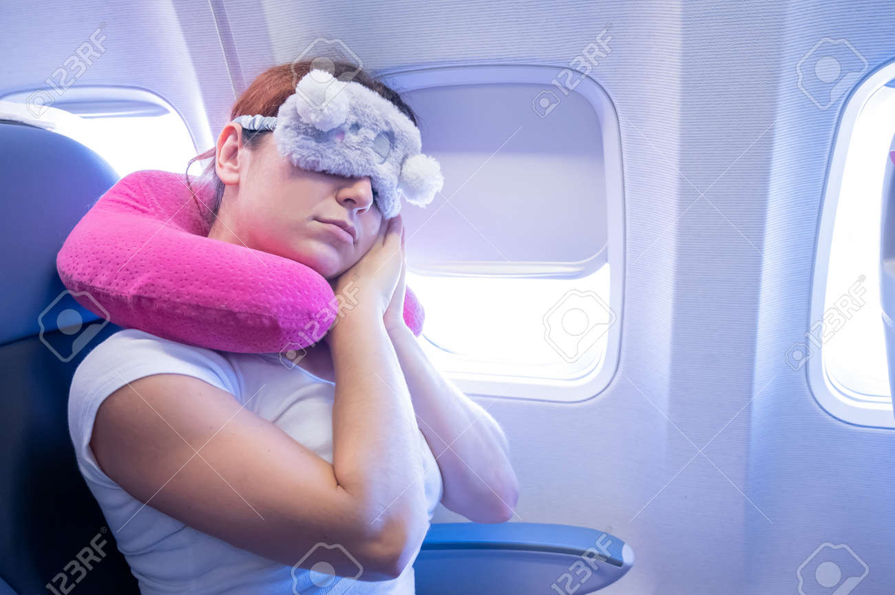 Tired red-haired woman sleeping on the plane with an eye mask and a neck pillow - 155611037