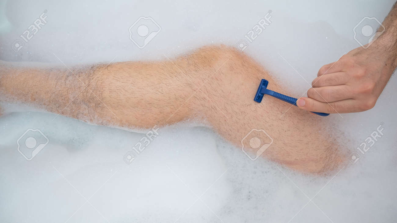 Funny picture of a man taking a relaxing bath and shaving his legs. Close-up of male feet in a bubble bath. Top view. - 170452696
