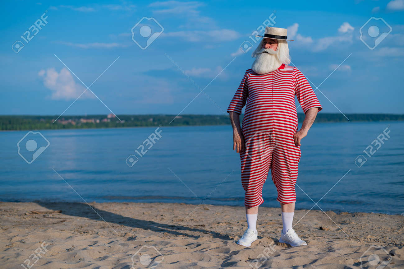An elderly man in a striped retro swim suit and Boater on the seashore - 170453202