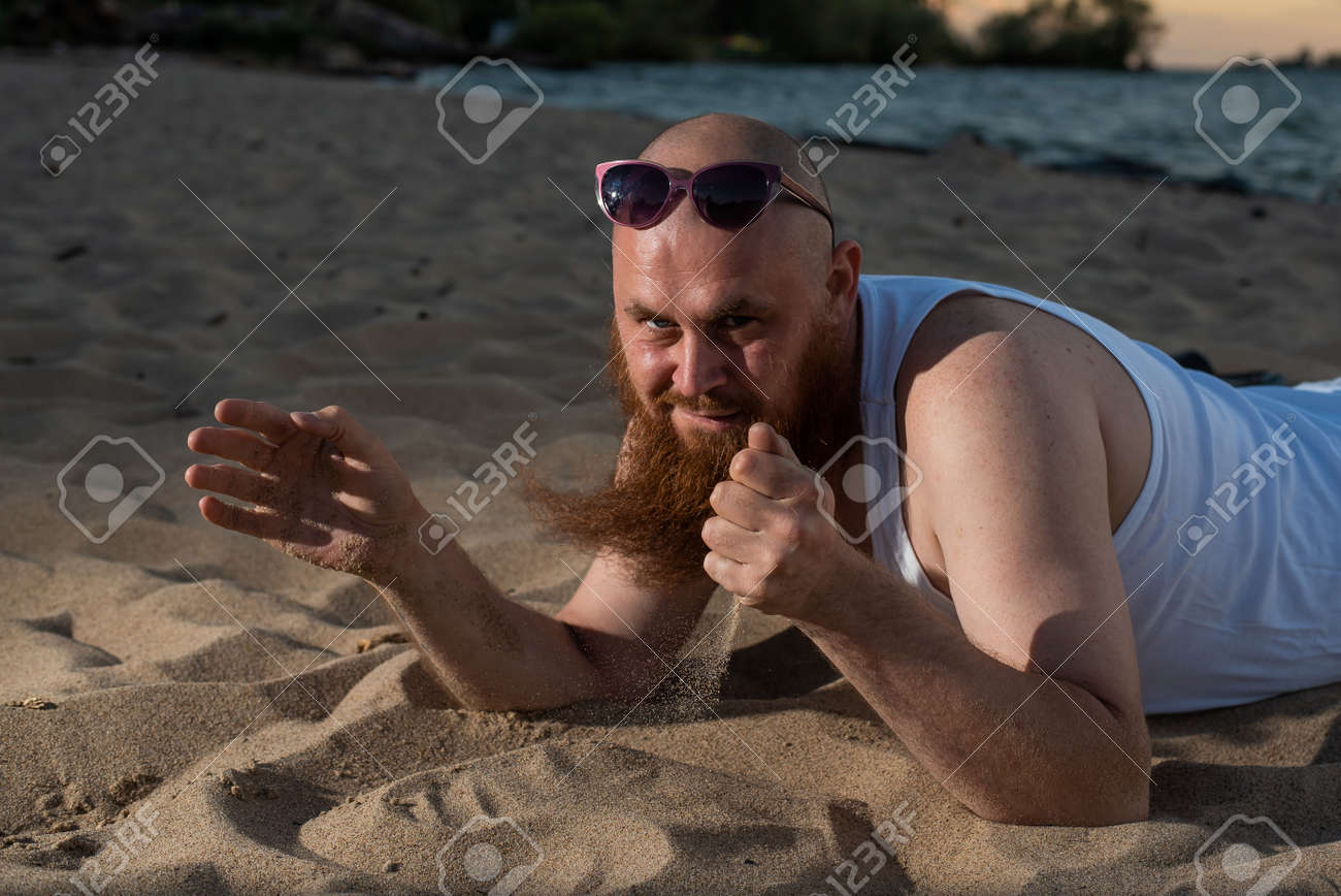 A humorous portrait of a brutal man in a T-shirt and boxers on the beach at sunset - 170455748